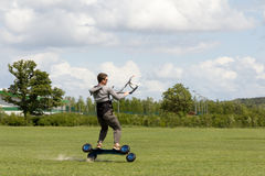 Wheelie-teenager kite boarding on two wheles on gr Stock Images