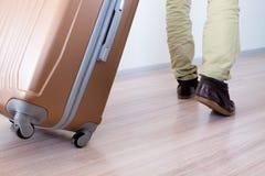 Wheeling big baggage. Young traveler wheeling his big and heavy luggage, moving forward for vacation Royalty Free Stock Photos