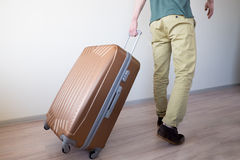 Wheeling big baggage. Young traveler wheeling his big and heavy luggage, moving forward for vacation Stock Photography