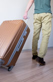 Wheeling big baggage. Young traveler wheeling his big and heavy luggage, moving forward for vacation Royalty Free Stock Photography