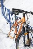 Wheelless oranje fiets die aan de ijzeromheining wordt vastgebonden stock afbeeldingen