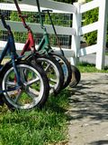Wheels of amish children`s scooters. Unique perspective of the wheels and scooters of Amish children, waiting by the fence outside of the schoolhouse royalty free stock images
