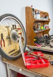Wheels and bicycle parts over workshop table Royalty Free Stock Photography