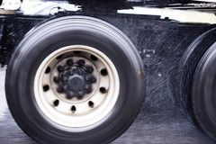 Wheels of big rig semi truck running in the rain dust. The twin wheels on the tandem axels of the large powerful big rig semi truck rotate during the movement Royalty Free Stock Image