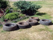 Wheels. Car wheels on ground near flower bed Royalty Free Stock Image