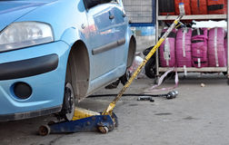 Wheels change. A blue car having its wheels replaced by a hydraulic jack Stock Images