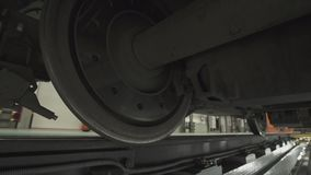 Wheels on chassis of train wagons at workshop in factory. Modern transportaion concept stock footage