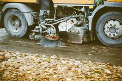 Wheels detail of in motion orange street sweeper. Truck on the street working cleaning autumn foliage Royalty Free Stock Photos