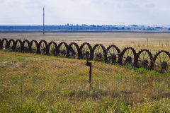 Wheels on the field. Fence and fence of old wheels on the field Royalty Free Stock Images