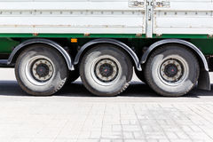 Wheels of large truck and trailers at parking lot. Closeup view Stock Photos