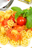 Wheels of pasta with fresh tomatoes Royalty Free Stock Photo