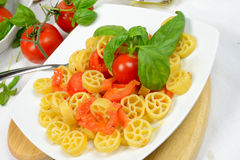 Wheels of pasta with fresh tomatoes Royalty Free Stock Images