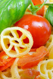 Wheels of pasta with fresh tomatoes Stock Image