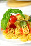 Wheels of pasta with fresh tomatoes Royalty Free Stock Image