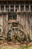 Wheels and Rims From an Old Wagon. An old building with weathered wagon wheels and rusty rims leaning against it Royalty Free Stock Images