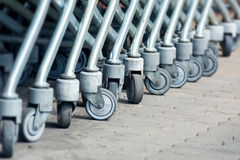 Wheels of shopping carts in a diagonal row, selected focus Royalty Free Stock Image