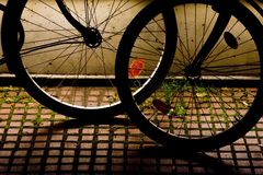 Wheels silhouette. Silhouette of bicycles wheels at night light Stock Image