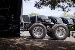 Wheels with tires of black big rig semi truck with five wheel on. Powerful stylish black big rig semi trucks with black semi trailers are lined up in an open Royalty Free Stock Photos