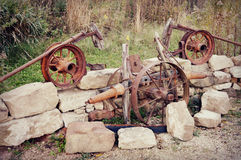 Wheels and Tools. Antique wheels and tools displayed amidst some large stones Royalty Free Stock Images