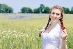 年轻美丽的妇女在绿色wheet领域的愉快的微笑的&看的照相机在夏日 免版税库存图片