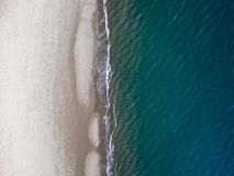 Where the Beach meets the Sea. An aerial view of waves breaking onto a beach in Norfolk royalty free stock image