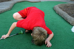 Where'd It Go?. A little boy looks into the cup on a miniature golf course Stock Photography
