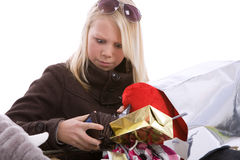 Where did all the money go?. Young teenage girl surrounded by shopping bags looking shocked into her wallet Royalty Free Stock Photography