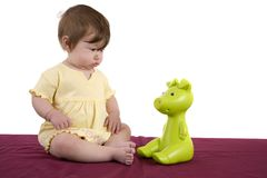 Where did that come from. Cute little baby girl looking very surprised at a toy sitting next to her Stock Images