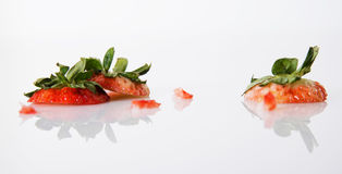 Where did the strawberries go?. Strawberry tops on white with a reflection and studio light. Too delicious not to eat Stock Photography
