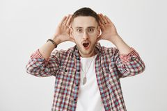 Where did you hear that from. Shocked and interested young handsome male with bristle in trendy eyewear holding palms. Near ears to listen carefully, standing Royalty Free Stock Images
