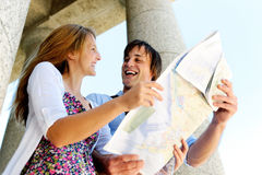Where do we go next?. Smiling couple laughs at each other while looking at a map stock photo