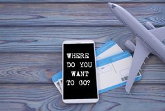 Where do you want to go? screen of the mobile phone, air tickets, airplane. Modern technology, applications for smartphones, online flat concepts. on a wooden stock image