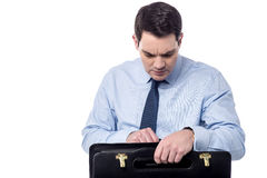 Where is the documents ?. Tensioned businessman searching documents in his bag stock image