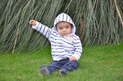 Where does this baby. A naive child in green nature Stock Photos