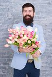 Where dreams become reality. Womens day. Flower for March 8. Spring day. Bearded man with flowers. Bearded man with royalty free stock image