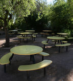 Where is everybody 2. Wide angle of abandoned yellow pinic tables stock image