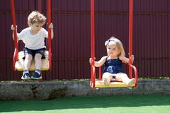Where we grow up. Small children with blond hair on swing. Small brother and sister enjoy playing together. Girl and boy. Haircut styles. Hair salon for stock photos
