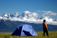 Where am I going Today. Adult male next to tent in scenic mountain setting contemplating his journey Stock Photos
