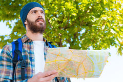 And where I have to go?. Thoughtful young man carrying backpack and holding map Royalty Free Stock Photos