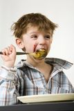 Where is my big spoon?. Shaggy boy eating with table spoon Royalty Free Stock Photo