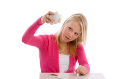 Where is the rest. Cute teenager holding her piggybank upside to check if it is empty Royalty Free Stock Photography
