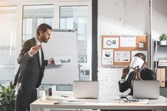 Skilled manager is gesturing with annoyance. Where is result. Young angry bearded men is standing with report and looking at employee with irritation. His Royalty Free Stock Image
