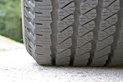 Where the rubber meets the road. Close up of auto tire in contact with the road royalty free stock photos