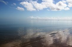 Where the sea ends and the sky begins. Clouds reflected in the wet sand and the flat calm sea. It's hard to know where the sea ends and the sky begins Stock Image