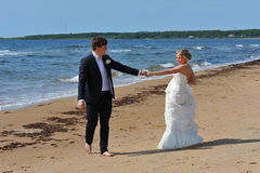 Where shall we go?. The young couple have different opinions of where to go on the beach but the expression in the eyes of the bride will soon convince the groom Royalty Free Stock Photography
