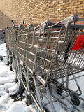 Where shopping carts go to die. A bunch of old shopping carts, with a brick wall in the background, surrounded by snow Stock Photos