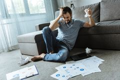 Unhappy stressed out man working at home. Where is solution. Unhappy stressed out handsome man sitting on the floor and looking for a solution to the problem Royalty Free Stock Photography