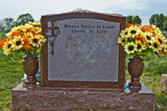 Where there is Love. Memorial stone made of red granite. Inscription reads: Where There is Love There is Life. Spring / Summer flowers in the vases. Adornment in stock images