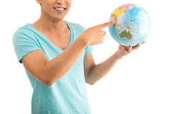 Where to go?. Cropped image of a young boy with a globe in hands over a white background Stock Image