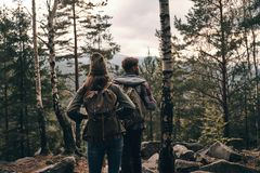Where to go next?. Rear view of young couple standing and looking away while hiking together in the woods Royalty Free Stock Photos